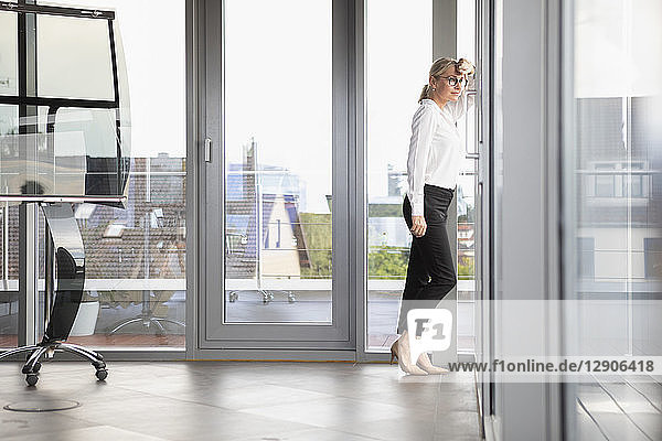 Successful businesswoman standing in office  looking out of window