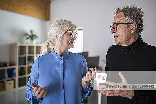 Two senior colleagues discussing in office