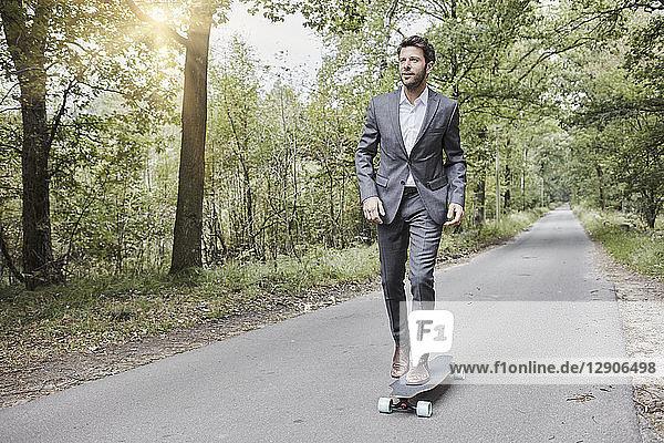 Businessman riding skateboard on rural road