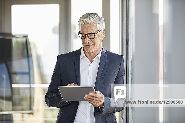 Businessman standing by window  using digital tablet