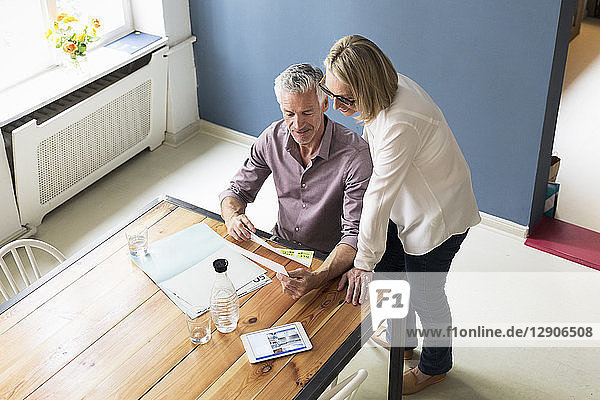 Mature couple with documents and tablet at home