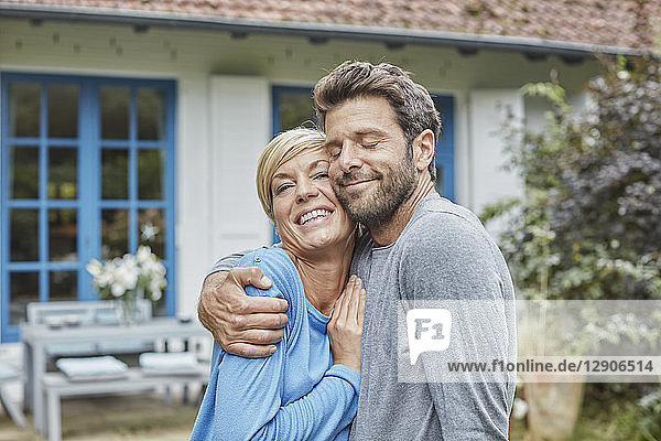 Happy couple hugging in front of their home
