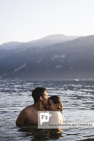 Affectionate young couple kissing in a lake