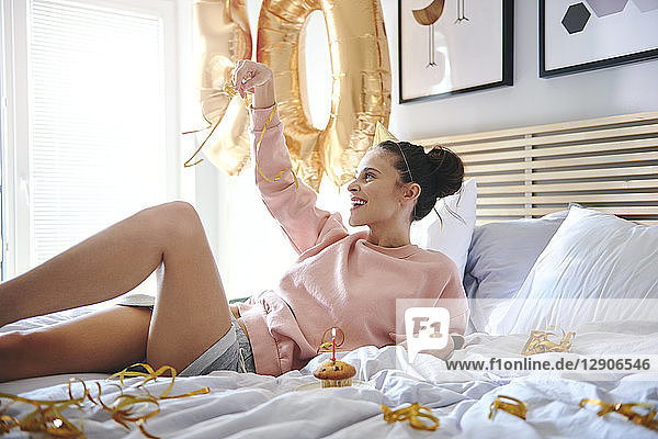 Cheerful woman celebrating her birthday in bed