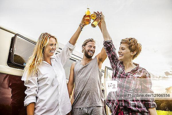 Happy friends clinking beer bottles at a van in rural landscape