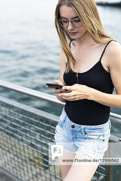 Young woman standing at East River  using smartphone
