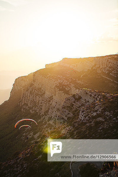 Spain  Silhouette of paraglider soaring high above the mountains at sunset