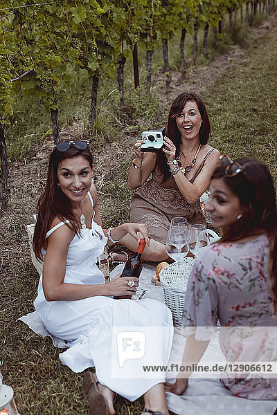 Friends having picnic in a vineyard  one woman taking pictures with instant camera