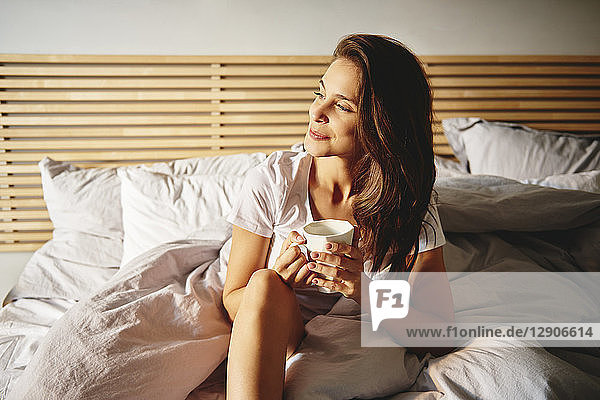 Portrait of smiling young woman sitting on bed with cup of coffee looking at distance