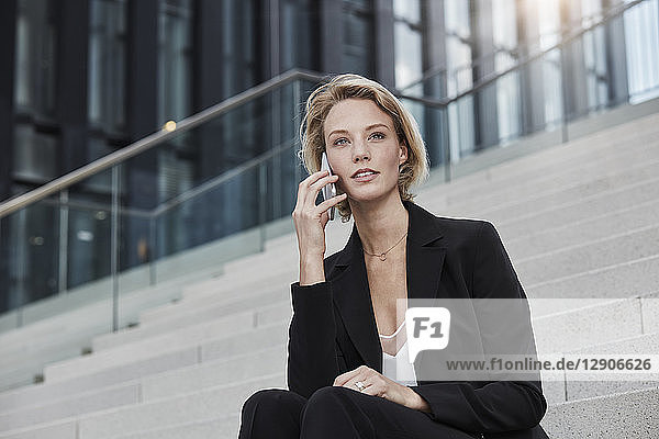 Portrait of young businesswoman on the phone sitting on stairs outdoors