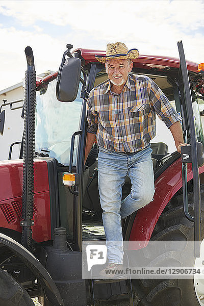 Portrait of smiling senior farmer getting out of tractor