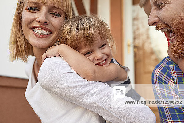 Close-up of happy family in front of their home