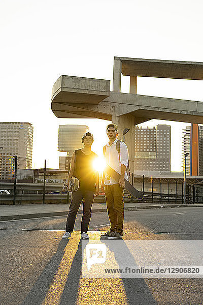 Portrait of two young men with skateboards in the city at sunset