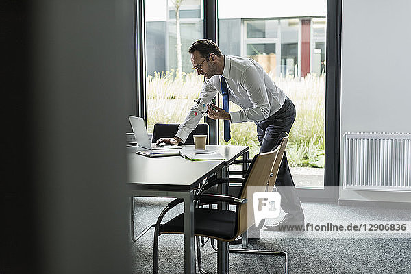 Businessman with atomic model using laptop in his office