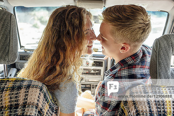 Romantic couple doing road trip  kissing in car