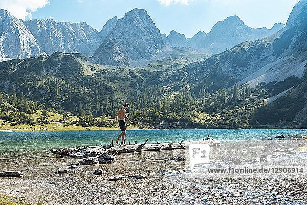Austria  Tyrol  Young man at Lake Seebensee balancing on tree trunk
