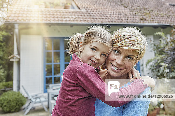 Portrait of smiling mother carrying daughter in front of their home
