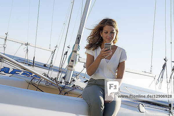 Beautiful woman sitting on a boat  using smartphone