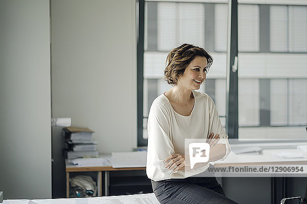 Successful businesswoman sitting on desk in her office