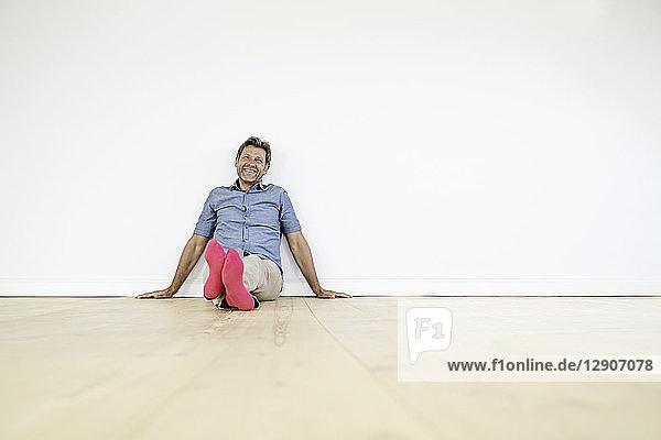 Mature man sitting on ground in empty room
