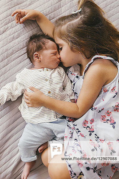 Affectionate girl lying on blanket cuddling with her baby brother Affectionate girl lying on blanket cuddling with her baby brother