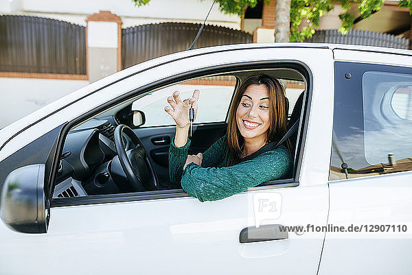 Woman in the interior of a car  looking happy at the keys