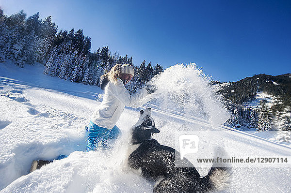 Austria  Altenmarkt-Zauchensee  happy young woman playing with dog in snow