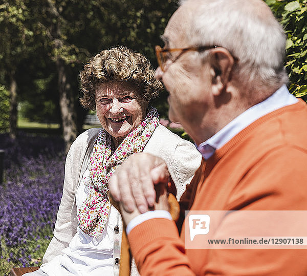 Senior couple sitting on bench in a park  talking