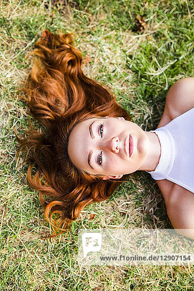 Portrait of redheaded young woman lying on a meadow