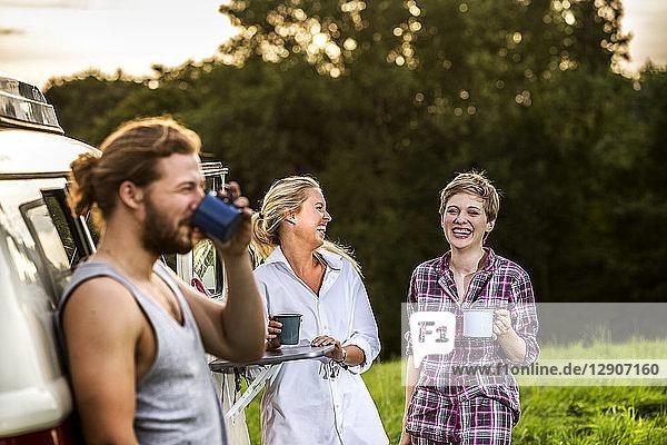 Carefree friends enjoying coffee at a van in rural landscape