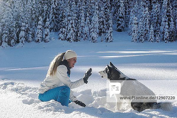 Austria  Altenmarkt-Zauchensee  young woman sitting with dog in snow