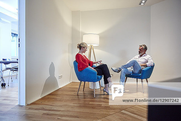 Mature man and young woman sitting in armchairs talking
