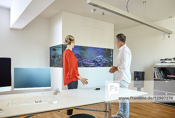 Mature man and young woman standing in office looking at aquarium