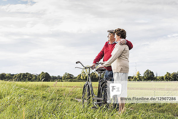 Senior couple with bicycles embracing in rural landscape