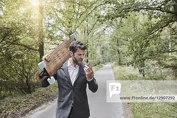 Angry businessman with skateboard shouting at smartphone on rural road
