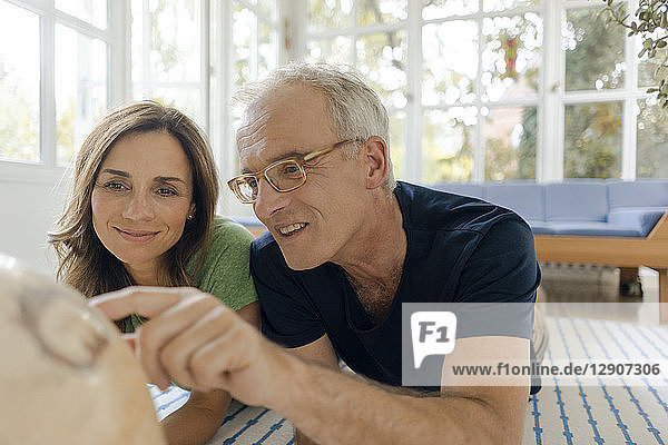 Mature couple lying on the floor at home looking at globe