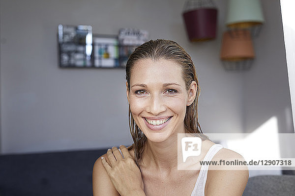 Portrait of laughing blond woman with wet hair at home