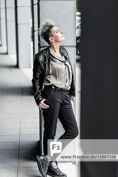 Punk woman leaning against a column looking up