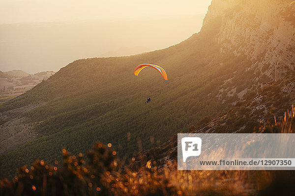 Spain,  Silhouette of paraglider soaring high above the mountains at sunset