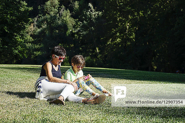 Mother and daughter taking photographs  sitting on grass
