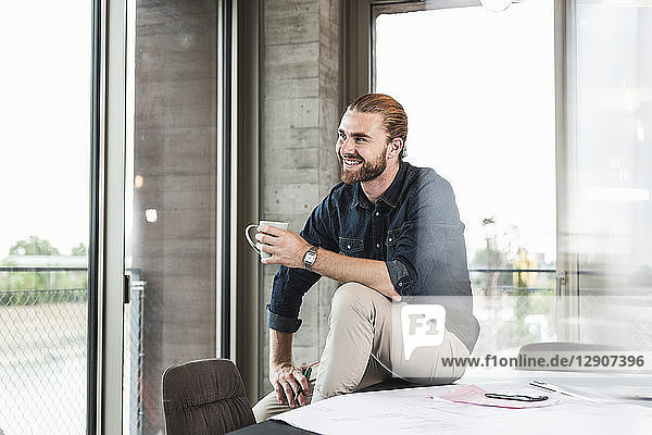 Smiling young businessman sitting on desk in office with cup of coffee