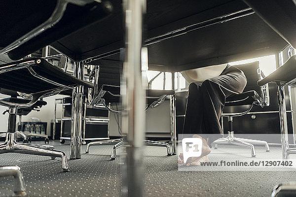 Bare feet of businesswoman under her desk