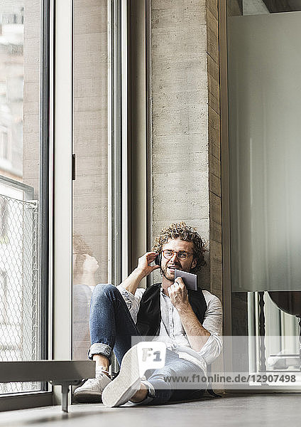 Casual young man sitting at the window with headphones and phablet