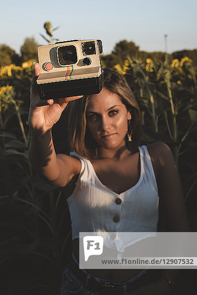 Young woman in a field of sunflowers holding an instant camera