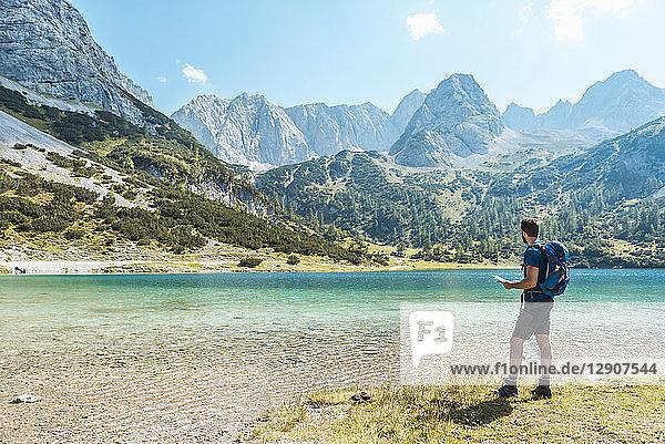 Austria  Tyrol  Man hiking at Seebensee Lake  looking at map