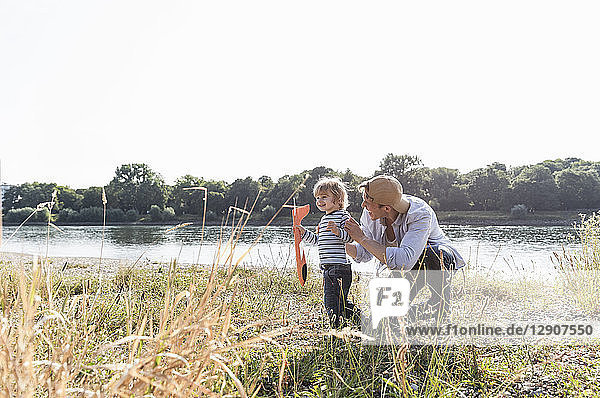 Father and son having fun at the riverside  playing with toy aeroplane