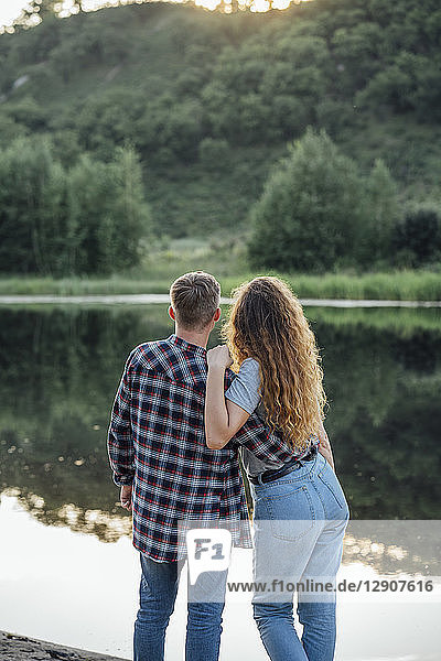 Romantic couple standing at the riverside  embracing