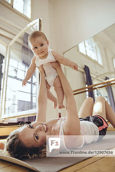 Mother working out on yoga mat while holding up her baby