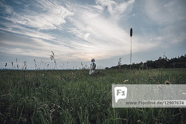 Spaceman exploring nature  standing in meadow  looking at sky