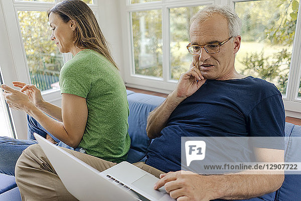 Mature couple sitting on couch at home with man using laptop and woman using cell phone